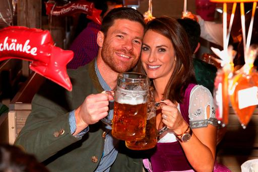 Bayern's Xabi Alonso, left, and Nagore Aramburo, right, pose for a photograph as the players of FC Bayern Munich visit the Oktoberfest beer festival 2015 at Theresienwiese in Munich, southern Germany, Wednesday, Sept. 30, 2015. (Alexander Hassenstein/pool via AP)