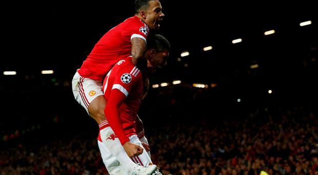 MANCHESTER, ENGLAND - SEPTEMBER 30: Chris Smalling of Manchester United (R) celebrates with team mate Memphis Depay as he scores their second goal during the UEFA Champions League Group B match between Manchester United FC and VfL Wolfsburg at Old Trafford on September 30, 2015 in Manchester, United Kingdom. (Photo by Dean Mouhtaropoulos/Getty Images)