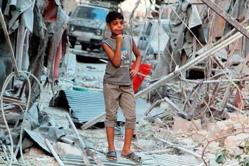 A boy inspects damage from what activists said was an airstrike by forces loyal to Syria's President Bashar-Assad in the al-Katerji district in Aleppo