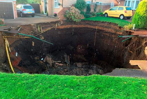 The giant hole spreads across the driveway and front garden of a property on Fontmell Close and is 10 metres deep. Photo credit should read: Hertfordshire Fire and Rescue/PA Wire