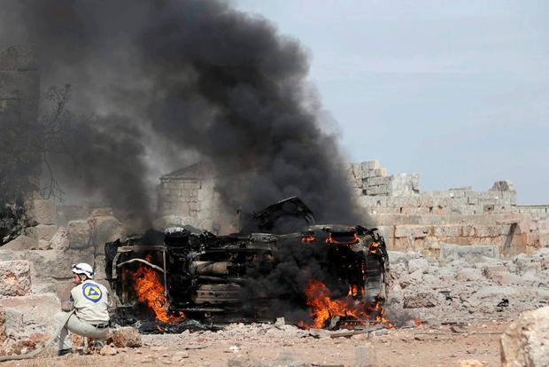 A civil defense member tries to put out the flames on a burning military vehicle at a base controlled by rebel fighters from the Ahrar al-Sham Movement that was targeted by what activists said were Russian airstrikes Credit: Khalil Ashawi (REUTERS)