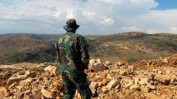 A Hezbollah fighter looks toward Syria from Lebanon (AP)