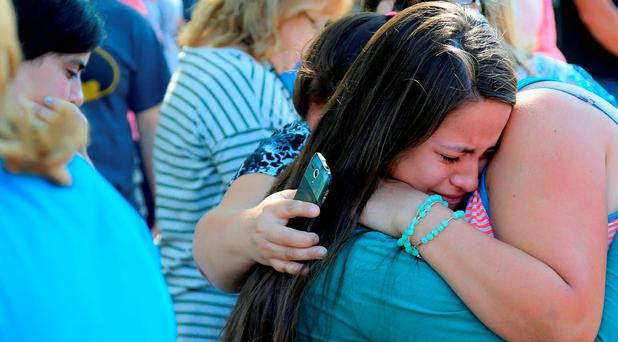 A woman is comforted as friends and family wait for students at the local fairgrounds after a shooting at Umpqua Community College in Roseburg, Oregon (AP Photo/Ryan Kang)