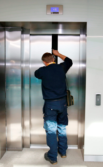 A lift engineer inspects the elevator doors after the Taoiseach and ministers got stuck Photo: Frank McGrath