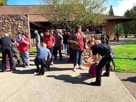 Police search students outside Umpqua Community College in Roseburg, Oregon, USA, after the shooting