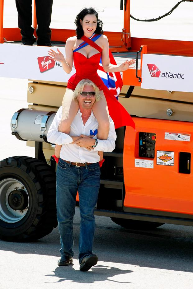 Founder and President of Virgin Group Sir Richard Branson carries burlesque artist Dita Von Teese on his shoulders after helping her down from a lift as they pose with a Virgin Atlantic Airways 747-400 aircraft at McCarran International Airport June 15, 2010