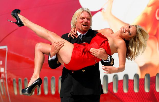 Virgin Atlantic boss Richard Branson poses with model Kate Moss on a wing of a jumbo jet at Heathrow Airport on June 22, 2009