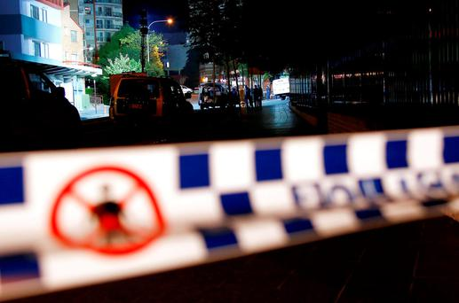 Australian police sealed off streets on Friday and warned the public to keep away from the police headquarters after two people were shot dead Credit: David Gray (REUTERS)
