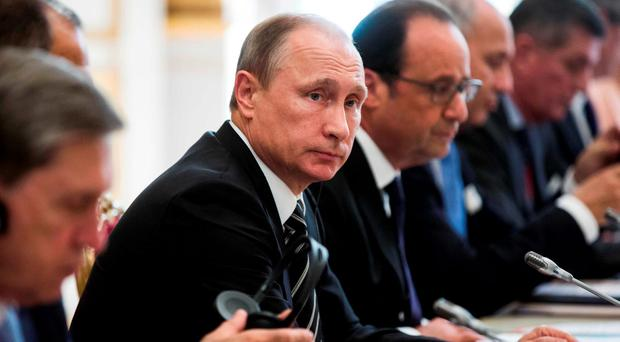 Russian President Vladimir Putin (L) and French President Francois Hollande sit together at the start of a summit on Ukraine at the Elysee Palace in Paris, France REUTERS/Etienne Laurent/Pool