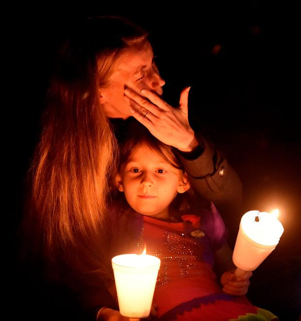 A woman cries while holding her daughter during a vigil in Roseburg, Oregon