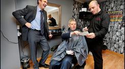 Renua Ireland's Michael O'Dowd canvassing alongside his campaign manager Thomas Clare (standing) with local barber Brendan O'Rourke in Dunleer, Co Louth Photo: Steve Humphreys