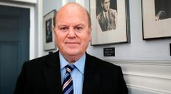 Finance Minister Michael Noonan beside a portrait of Michael Collins in the minister's meeting room in the Department of Finance yesterday Photo: Frank McGrath