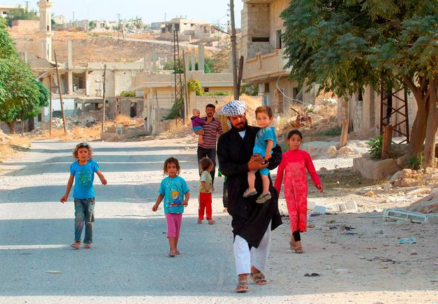 Civilians walk in Latamneh city that was hit on Wednesday by Russian air strikes, in the northern countryside of Hama, Syria October 2, 2015. REUTERS/Ammar Abdullah