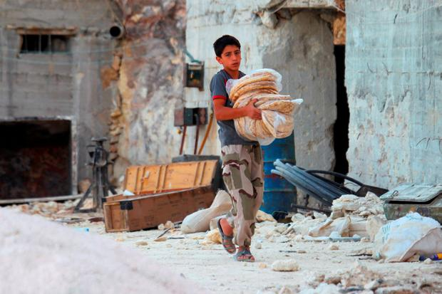 A boy carries bread as he walks in Latamneh city that was hit on Wednesday by Russian air strikes, in the northern countryside of Hama, Syria October 2, 2015. REUTERS/Ammar Abdullah