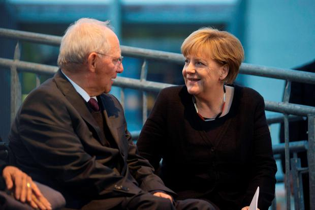 German Finance Minister Wolfgang Schaeuble (L) and German Chancellor Angela Merkel attend events to celebrate the 25th anniversary of German reunification in Berlin, October 3, 2015.REUTERS/Axel Schmidt