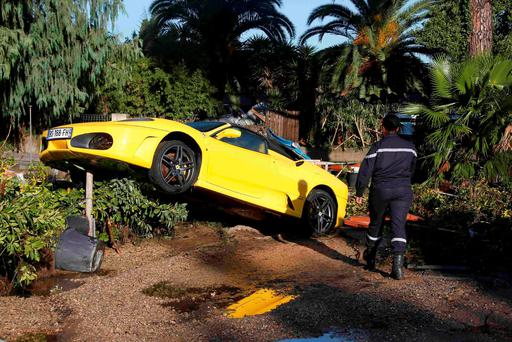 A French fireman walks near a damaged Ferrari after flooding caused by torrential rain in Biot, France, October 4, 2015. Reuters/Eric Gaillard
