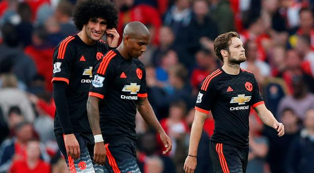 Manchester United's Daley Blind, Ashley Young and Marouane Fellaini (L) looks dejected at the end of the match