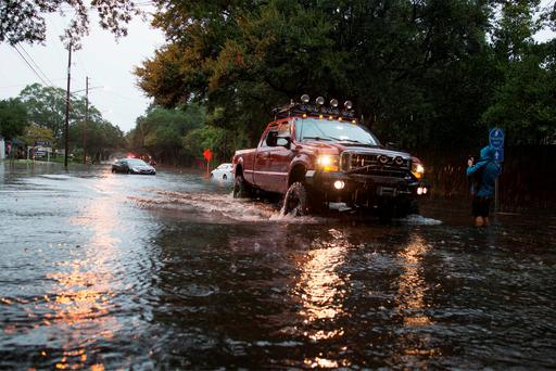 An all-terrain vehicle navigates along flooded Church Street in Georgetown, South Carolina October 4, 2015. Most major roads through the historical South Carolina city have closed due to flooding. REUTERS/Randall Hill