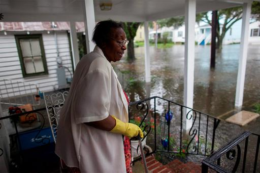 Ammie McKnight watches the level of floodwaters in the front yard of her Orange Street home in Georgetown, South Carolina October 4, 2015. Most major roads through the historical South Carolina city have closed due to flooding. Vast swaths of U.S. Southeast and mid-Atlantic states were grappling with heavy rains and flooding from a separate weather system which has already caused at least five deaths, washed out roads and prompted evacuations and flash flood warnings. REUTERS/Randall Hill