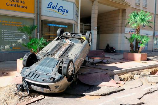 A damaged car is pictured on Boulevard de La Republique in downtown Cannes, southeastern France, on October 4, 2015 after violent storms and floods struck the French Riviera overnight, killing at least 16 people with four others missing, French authorities said. AFP PHOTO / JEAN LIOUJEAN LIOU/AFP/Getty Images