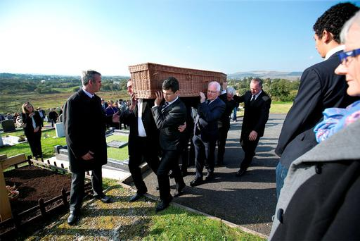 Family and friends carry the remains of Brian Friel to the graveside for the burial ceremony at Glenties Cemetary, Co Donegal.