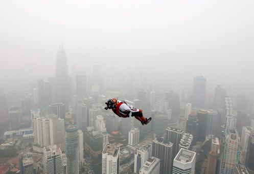 A BASE jumper leaps from the 300-metre high Kuala Lumpur Tower during the International Tower Jump in which more than 100 people take part, on a hazy day in Kuala Lumpur, Malaysia October 2, 2015. REUTERS/Olivia Harris