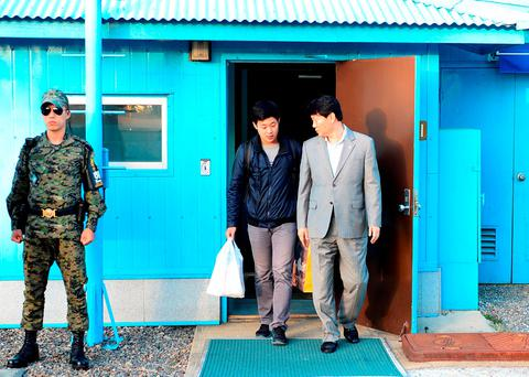 This handout photo released by the South Korean Unification Ministry and taken on October 5, 2015 shows Joo Won-Moon (C), a 21-year-old with permanent US residency, repatriated through the border truce village of Panmunjom on the inter-Korean border. AFP PHOTO / South Korean Unification Ministry