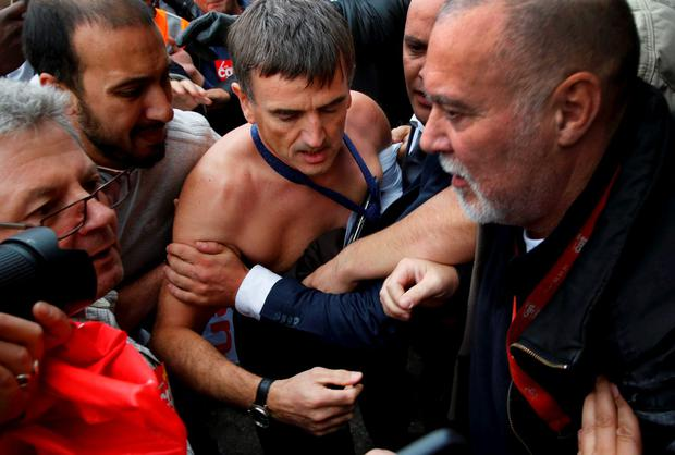 A shirtless Xavier Broseta (R) is evacuated by security Credit: REUTERS/Jacky Naegelen
