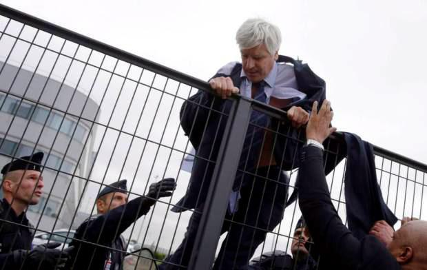 Director of Air France in Orly Pierre Plissonnier tries to cross a fence, helped by security and police officers, after several hundred of employees invaded the offices of Air France KENZO TRIBOUILLARD (AFP/Getty Images)