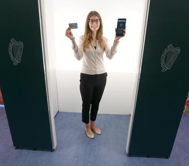 Amy Scully holds the new passport card and a phone with the new passport app at its launch. Photo: Damien Eagers