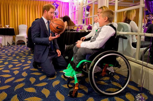 Prince Harry holds a basketball given to him by Toby Sweeney-Croft (right), 9, Inspirational Young Person Award winner in the 7-10 years-old age group, alongside his mother Rebecca (second right), as he attends the WellChild Awards in London. Credit: Justin Tallis/PA Wire