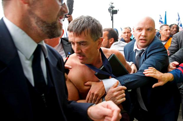 A shirtless Xavier Broseta (C), Executive Vice President for Human Resources and Labour Relations at Air France, is evacuated by security after employees interrupted a meeting with representatives staff at the Air France headquarters building at the Charles de Gaulle International Airport in Roissy, near Paris, France, October 5, 2015. REUTERS/Jacky Naegelen
