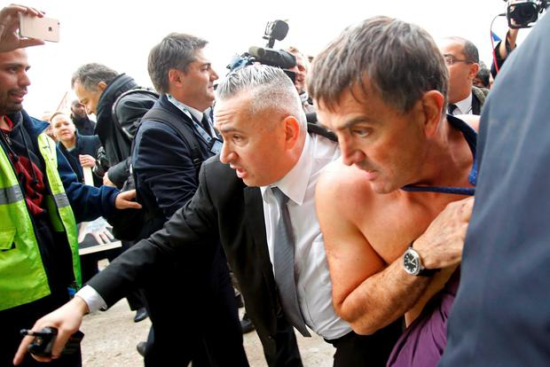 A shirtless Xavier Broseta (R), Executive Vice President for Human Resources and Labour Relations at Air France, is evacuated by security after employees interrupted a meeting with representatives staff at the Air France headquarters building at the Charles de Gaulle International Airport in Roissy, near Paris, France, October 5, 2015.