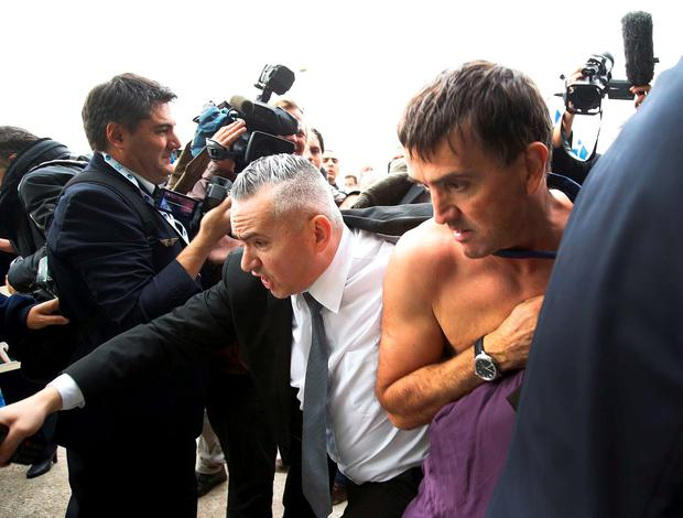 A shirtless Xavier Broseta (R), Executive Vice President for Human Resources and Labour Relations at Air France, is evacuated by security after employees interrupted a meeting with representatives staff at the Air France headquarters building at the Charles de Gaulle International Airport in Roissy, near Paris, France, October 5, 2015. REUTERS/Jacky Naegelen
