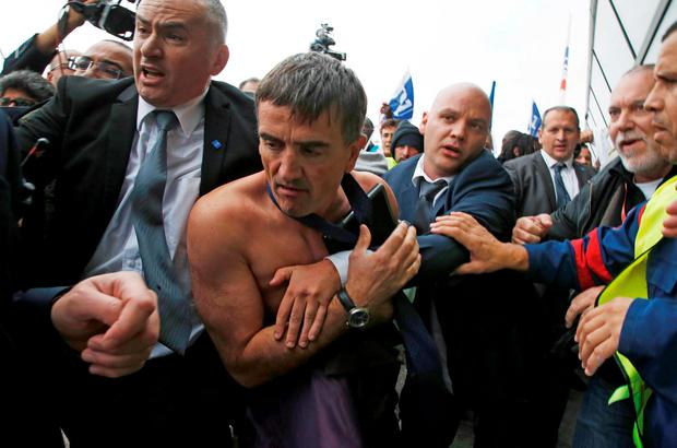 A shirtless Xavier Broseta (2ndL), Executive Vice President for Human Resources and Labour Relations at Air France, is evacuated by security after employees interrupted a meeting with representatives staff at the Air France headquarters building at the Charles de Gaulle International Airport in Roissy, near Paris, France, October 5, 2015. REUTERS/Jacky Naegelen