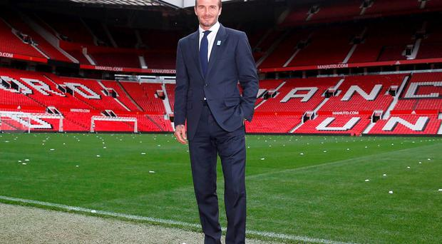 David Beckham poses for photographers at Old Trafford, ahead of his upcoming charity soccer match against a Rest of the World team led by Zinedine Zidane at Old Trafford to raise awareness and funds for UNICEF
