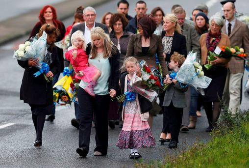 The wife of killed police officer Dave Phillips, Jennifer (front center) and their children Abigail (front R) and Sophie lead mourners as they arrive to lay floral tributes at Wallasey Dock Road where Phillips was struck and killed by a car in Wallasey, Britain October 7, 2015. REUTERS/Andrew Yates