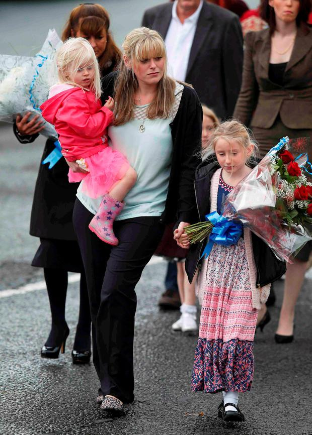 The wife of killed police officer Dave Phillips, Jennifer (center) and their children Abigail (R) and Sophie lead mourners as they arrive to lay floral tributes at Wallasey Dock Road where Phillips was struck and killed by a car in Wallasey, Britain October 7, 2015. REUTERS/Andrew Yates