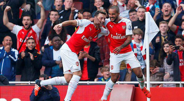 Mesut Ozil celebrates with Theo Walcott after scoring the second goal for Arsenal