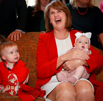 Abbey Boxshall (2) from Lucan watches as Tánaiste Joan Burton holds three-month-old Indie Rose Lyons from Malahide at the launch of the Labour Party Women's 'Lets Talk about Childcare' Report in the Merrion Hotel Photo: Frank McGrath