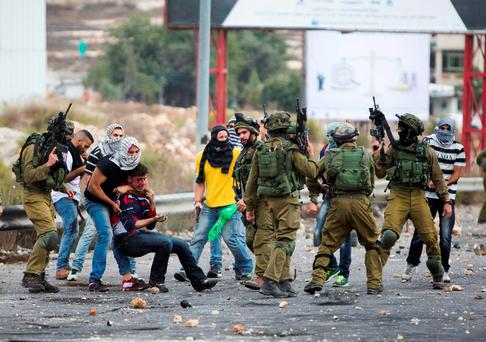 Undercover Israeli police officers and Israeli soldiers detain a wounded Palestinian demonstrator, being pulled up, during clashes near Ramallah, West Bank. Photo: AP