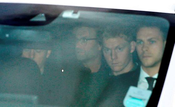 Jurgen Klopp (second left) is escorted away after arriving at John Lennon Airport, Liverpool today.