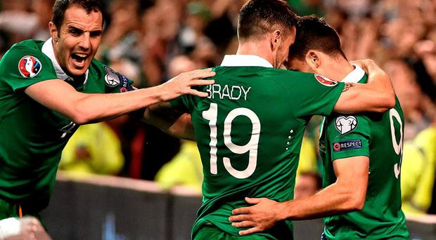 Republic of Ireland's Shane Long, right, celebrates with team-mates Robbie Brady, centre, and John O'Shea after scoring his side's first goal. UEFA EURO 2016 Championship Qualifier, Group D, Republic of Ireland v Germany. Aviva Stadium, Lansdowne Road, Dublin. Picture credit: David Maher / SPORTSFILE