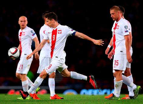 Robert Lewandowski of Poland celebrates with his team mates after scoring
