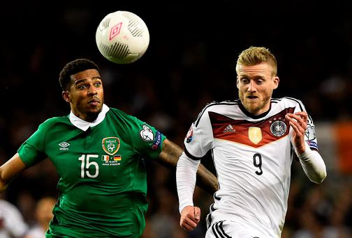 Republic of Ireland's defender Cyrus Christie (L) and Germany's midfielder Andre Schuerrle run for the ball