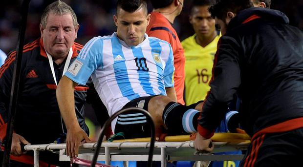 Argentina's forward Sergio Aguero is assisted by medical staff during their Russia 2018 FIFA World Cup qualifiers match against Ecuador, at the Nacional stadium in Santiago de Chile