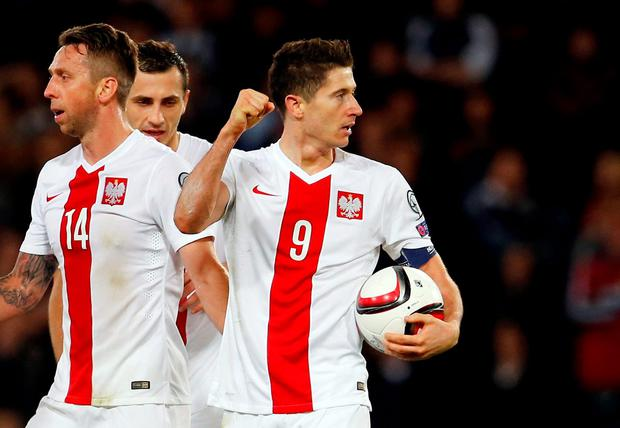 Robert Lewandowski celebrates with team mates after scoring the second goal for Poland