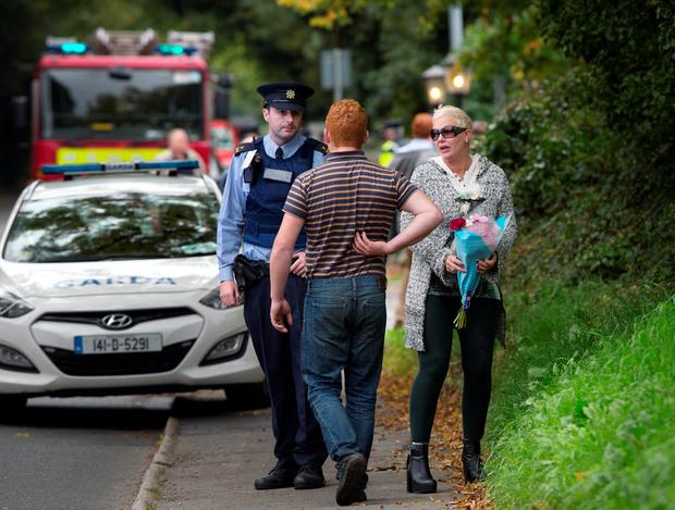 A well wisher brings flowers at the scene of the tragic fire at Glenamuck Road, Carrickmines, this morning. Photo: Tony Gavin.