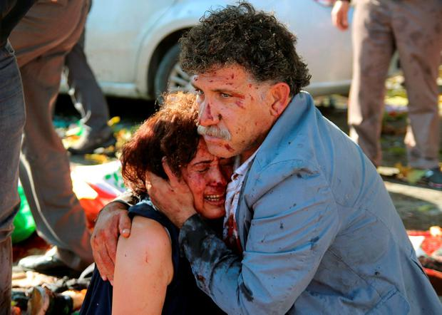An injured man hugs an injured woman after an explosion during a peace march in Ankara, Turkey Credit: Tumay Berkin ( REUTERS)