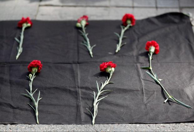 Carnations are seen placed on the ground during a protest against explosions at a peace march in Ankara, in central Istanbul, Turkey, October 10, 2015. REUTERS/Osman Orsal